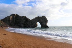 Durdle Door arch and beach with people walking