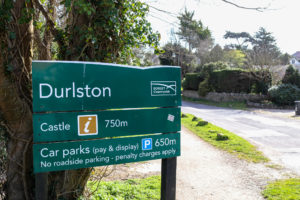 Welcome sign for Durlston Country Park near the woodland entrance