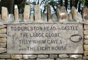Durlston head and castle sign carved into stone wall