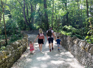 Family walking through a woodland path at Durlston Country Park