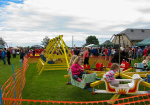 Traditional swing boats and roundabout at Harman's cross village field day