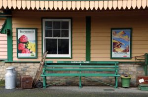 Bench and vintage style poster at Harman's Cross station