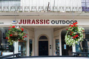 Hanging baskets at the entrance to Jurassic Outdoor on High Street in Swanage