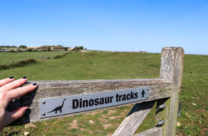 Hand pushing gate with Dinosaur tracks sign open at Keate's Quarry, Worth Matravers