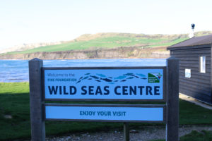 Kimmeridge Wild Seas Centre sign with the bay in the background