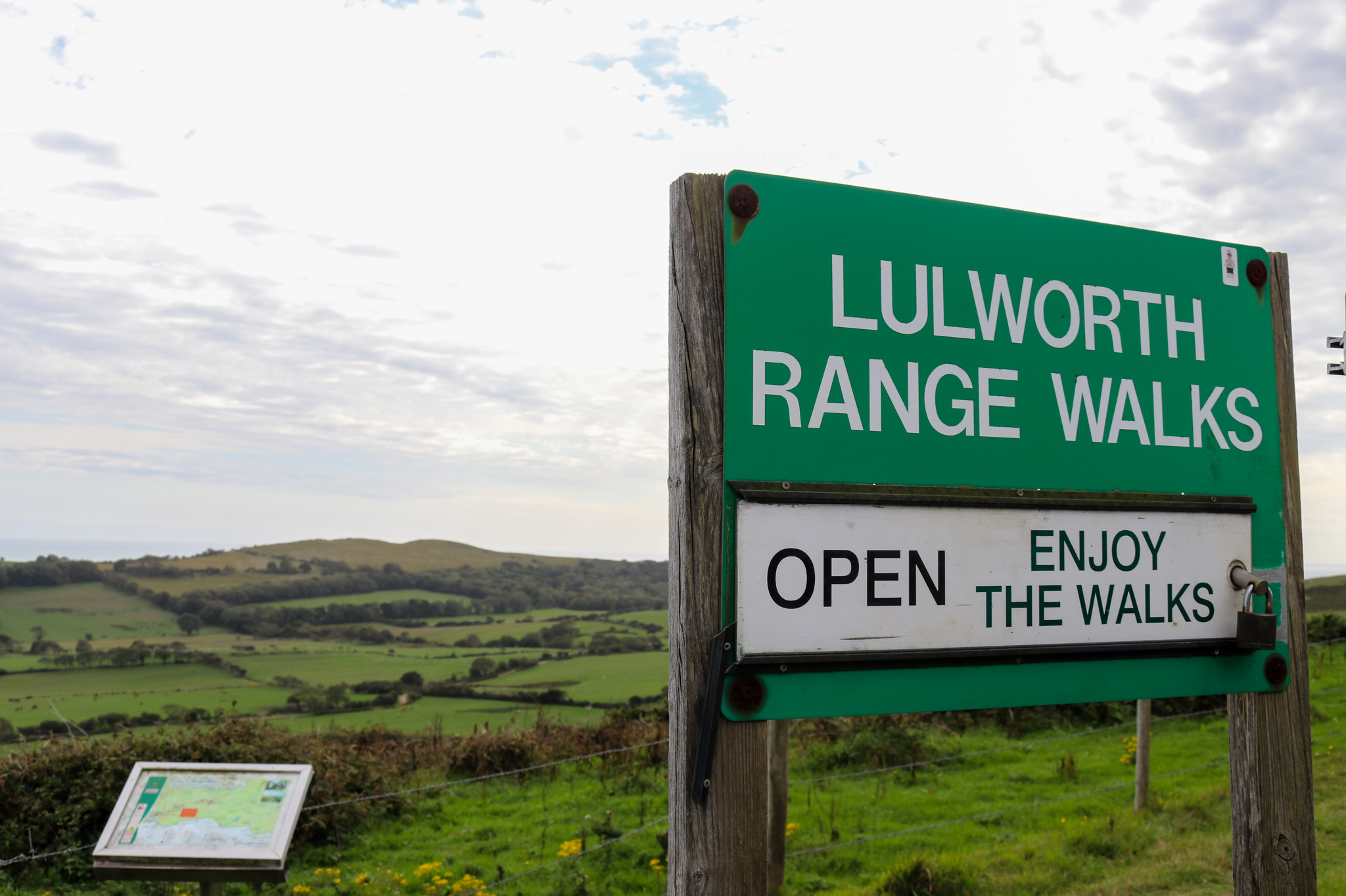Lulworth Range walks sign with Purbeck hills in distance