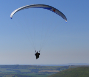 Person paragliding above Purbeck