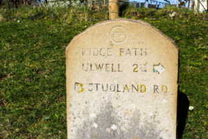 Stone sign on the Purbeck Ridgeway showing directions to Ulwell and Studland Road
