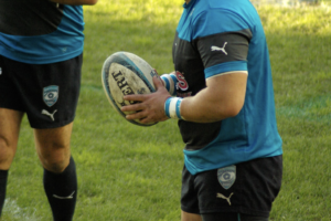 Man holding rugby ball on pitch