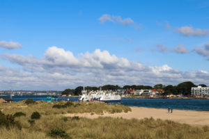 People walking on Shell Bay with Sandbanks Ferry behind