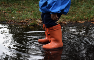 Red wellington boots splashing in puddle