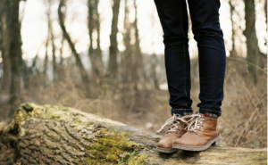 Person standing on log in forest