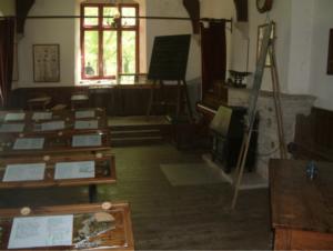 Desks and blackboard inside Tyneham schoolroom