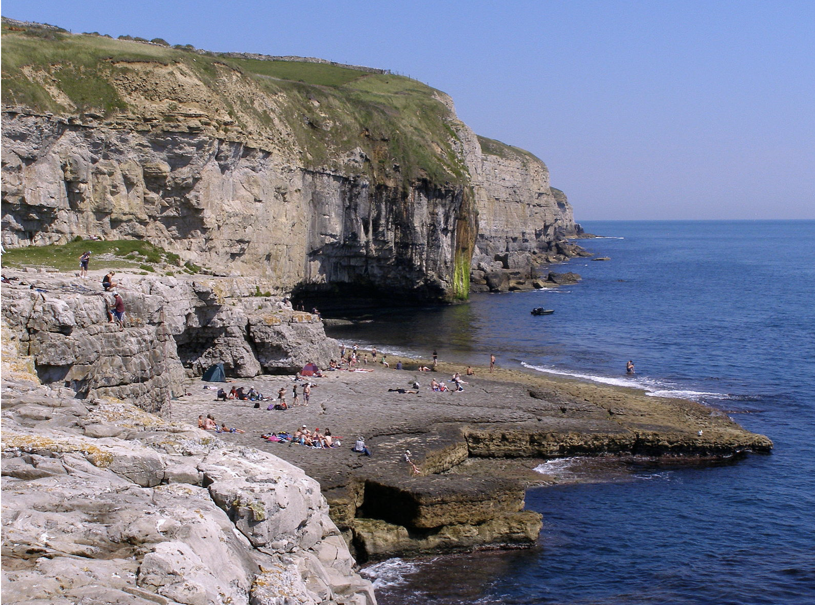 People sitting and sunbathing at Dancing Ledge