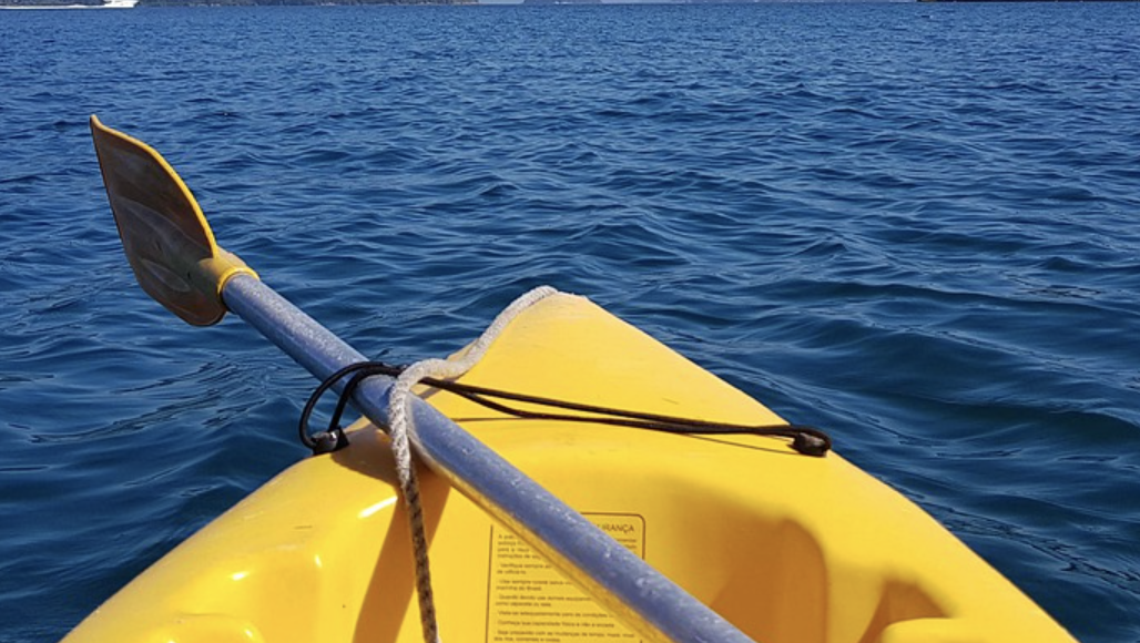 Yellow kayak and oar on sea