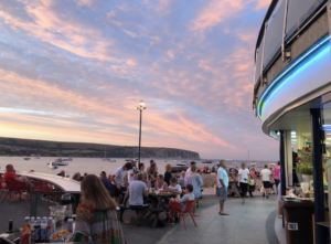 People eating at Gee Whites in Swanage at sunset