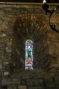 Stained glass window inset into wall in Studland's St Nicholas' Church