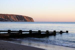 Sunset with Swanage Beach groyne and Ballard Down