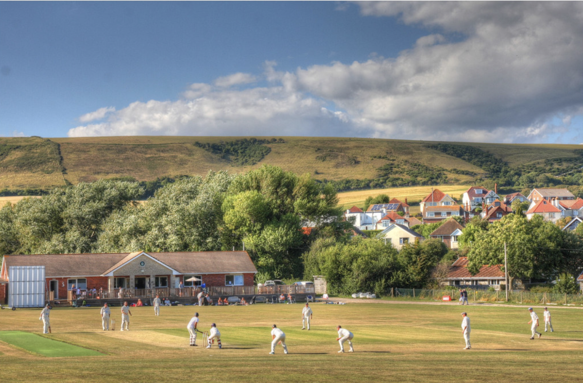 Cricketers at Swanage Cricket Club with Purbeck Hills in distance