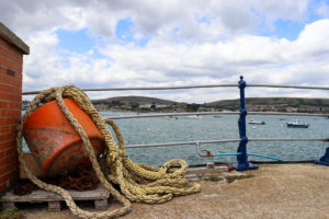 Rope and buoy on Swanage Pier with view of Purbeck Hills