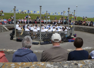 People watching The Swanage Town band play in a roofless bandstand