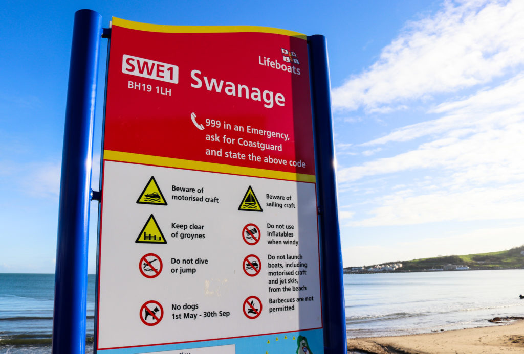 Swanage beach safety coastguard sign with strand behind