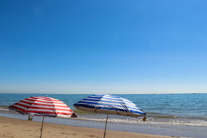 Red and blue striped umbrellas at Swanage Beach in the sunshine