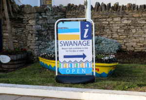 Swanage information centre sign in front of yellow boat planter