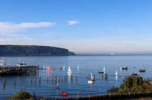 Sailing boats on the water by Swanage Old Pier