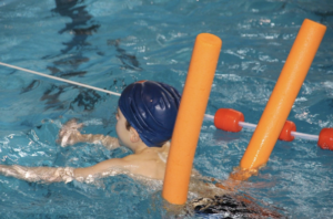 Boy swimming in a pool with a noodle