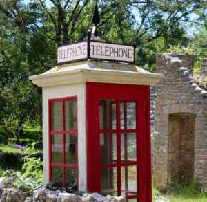 Red and white vintage telephone box replica in Tyneham village
