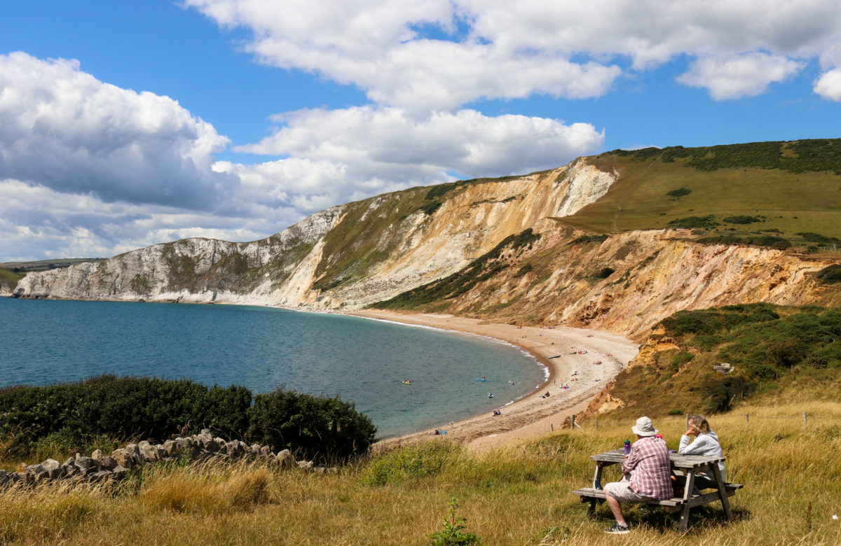 Couple sitting at a picnic table overlooking Worbarrow Bay