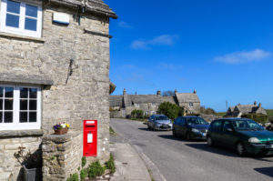Red postbox set into wall on street in Wroth Matravers village