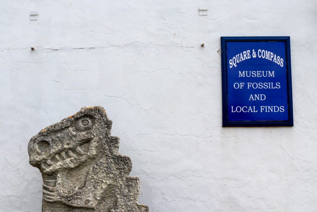 Dinosaur sculpture and Worth Matravers fossil museum sign