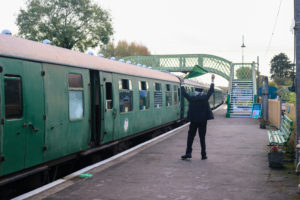 Volunteer conductor waving a diesel train off with a flag from Corfe Castle station