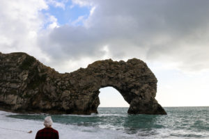 Boy in a white bobble hat looking at Durdle Door from beach
