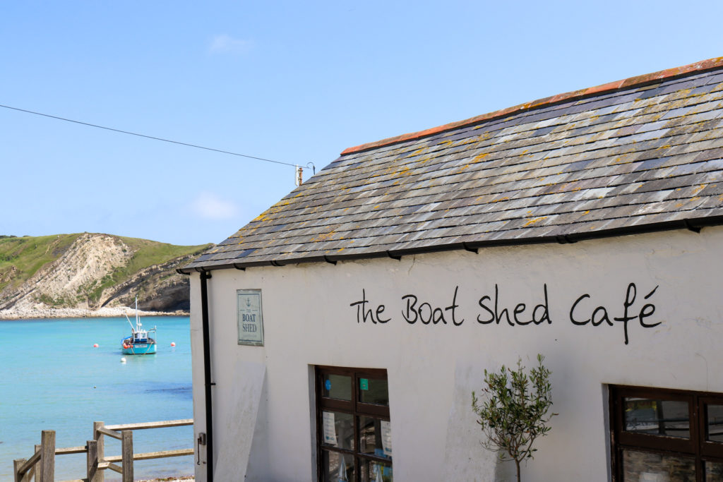 Boat in water by The Boat Shed cafe in Lulworth Cove