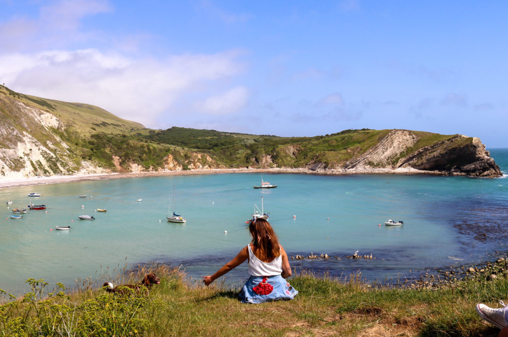 Woman and puppy looking at boats in Lulworth Cove