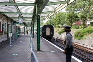 Man in overalls and hat on Swanage train platform