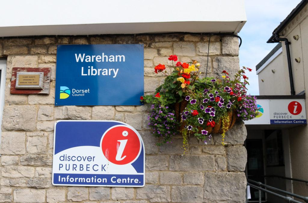 Signage and hanging basket outside Wareham library