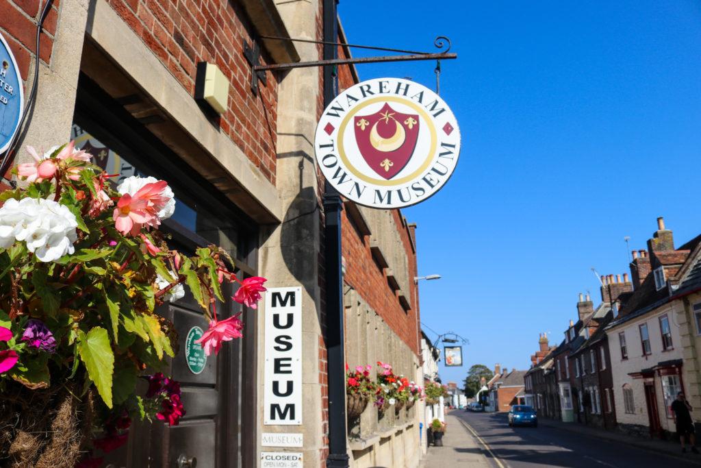 Wareham museum sign and hanging basket at Wareham town hall