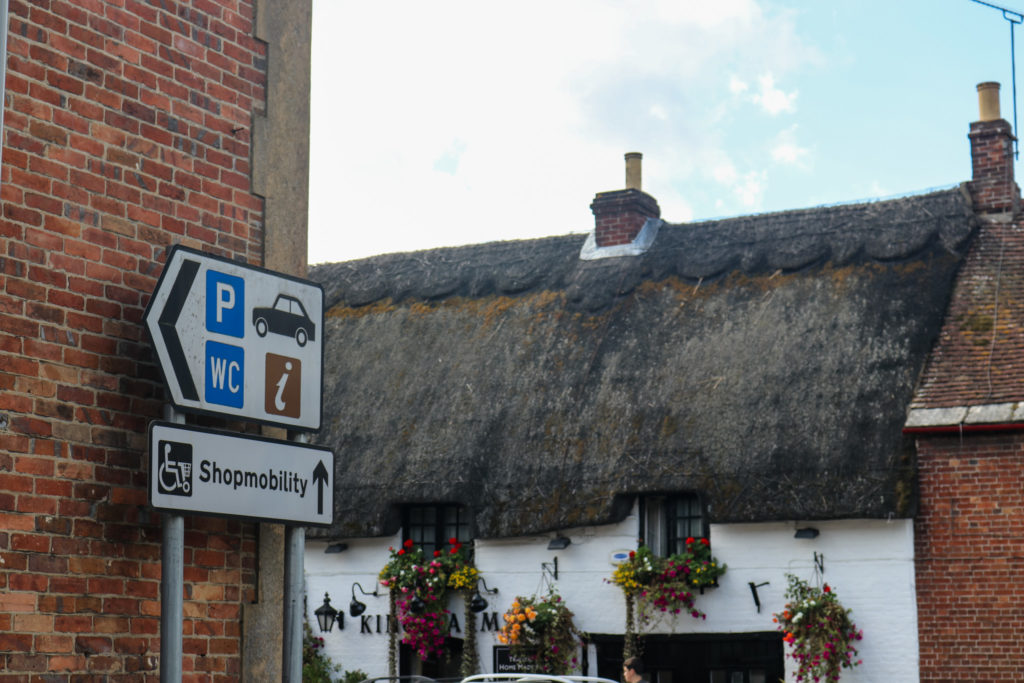 Parking and toilet sign in Wareham with thatched pub behind