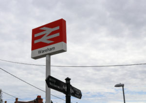 Wareham Station sign and bus stop walking route sign
