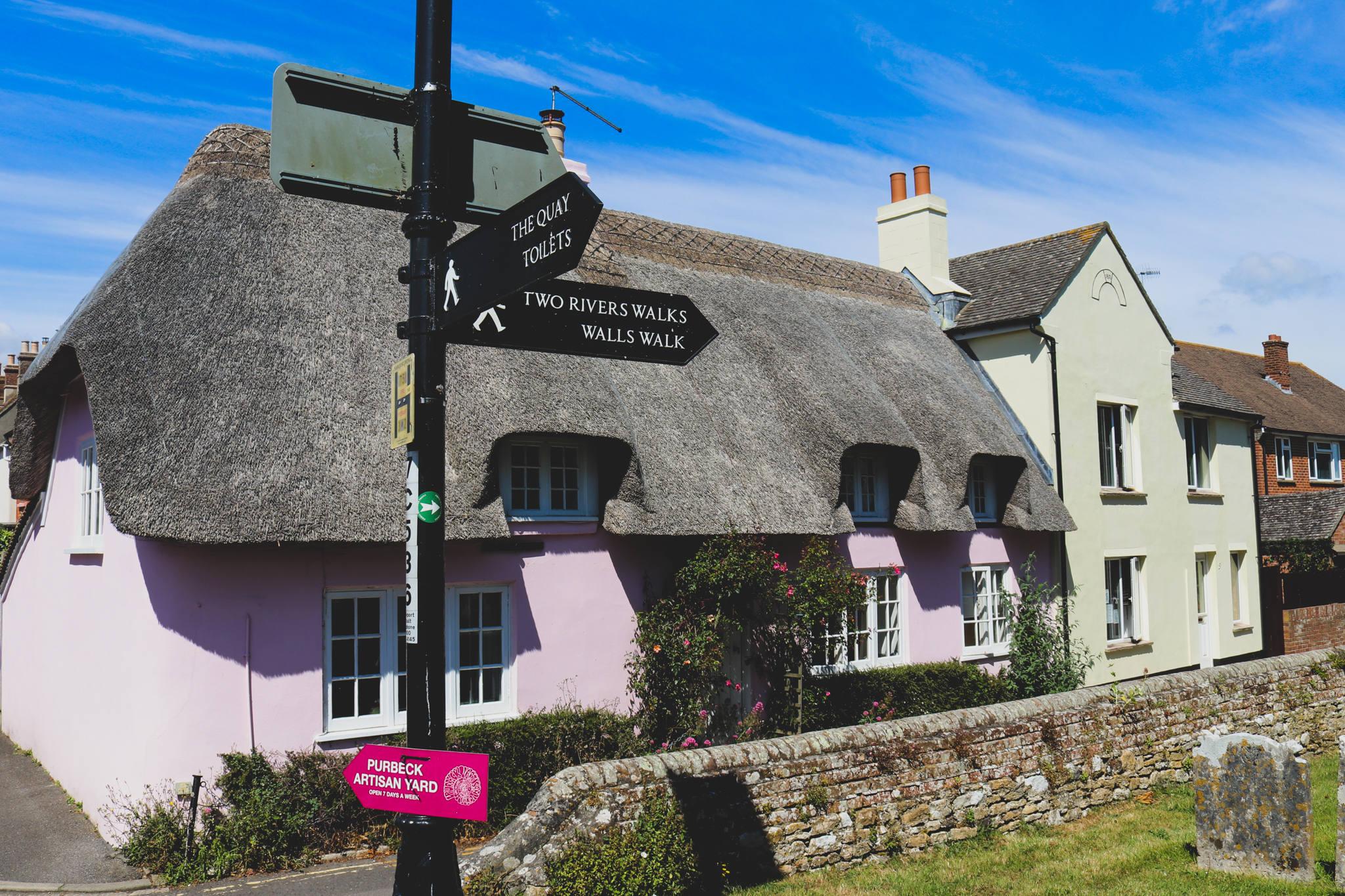 Pink thatched cottage and road signs in Wareham