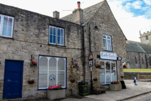 Exterior of Corfe Castle village store with church behind