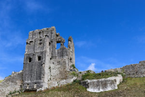 The ruined keep at Corfe Castle with blue sky behind