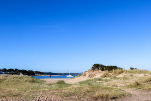 Sail boat in Poole Harbour by Shell Bay in Studland