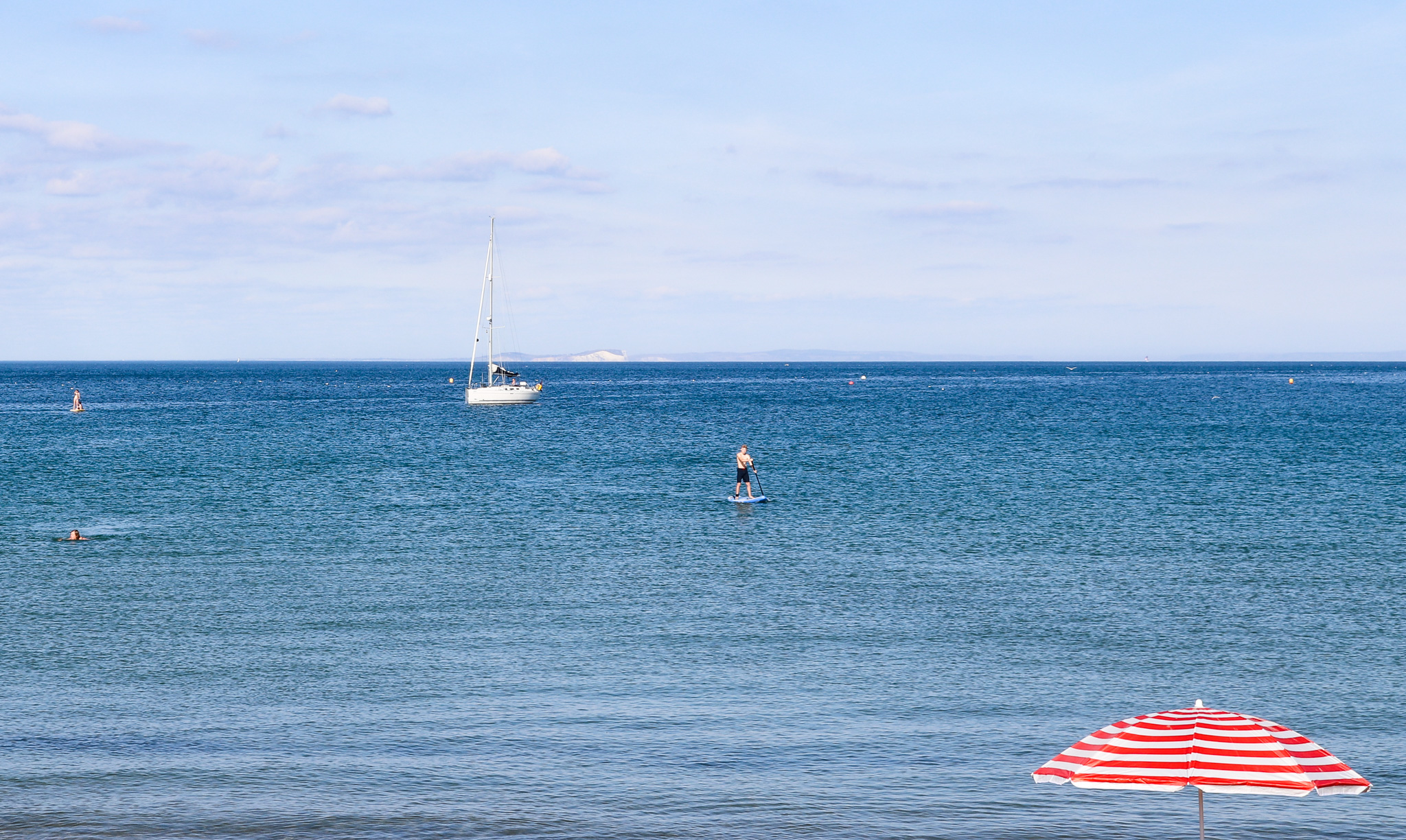 Stripy red and white parasol and paddle boarder at Swanage Beach