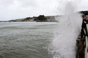 Woman watching storm waves in Swanage