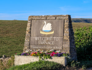 Welcome to Swanage sign with Purbeck Hills behind